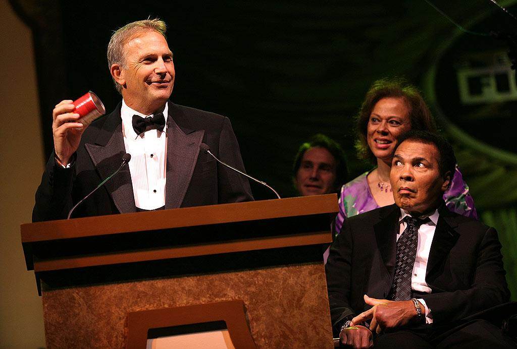 """Honoree Kevin Costner accepts the Muhammad Ali Achievement Award while the boxing great and his wife Lonnie look on. Jordan Strauss/<a href=""""http://www.wireimage.com"""" target=""""new"""">WireImage.com</a> - April 5, 2008"""