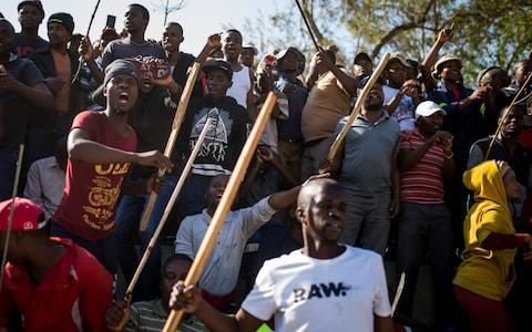 A group of Zulu men residing at the Jeppe Hostel shout and wave stick during a speech given by the Police Minister General Bheki Cele in JeppesTown - Credit: GUILLEM SARTORIO/AFP