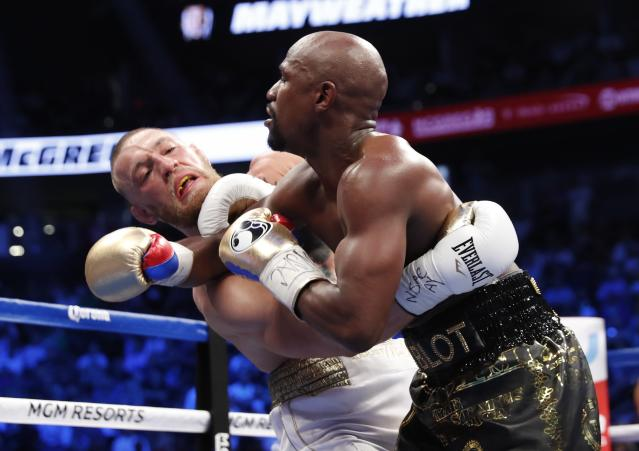 <p>Floyd Mayweather Jr. in action with Conor McGregor REUTERS/Steve Marcus </p>