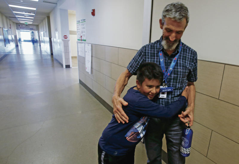 In this Sept. 19, 2019 photo, Gary Bass gets a hug in Santa Fe, new Mexico, from Jose Rodrigo Pena Ruiz, 10, a fifth grade student who wanted to know when he was going to Cambodia. The digital literacy teacher at El Camino Real Academy in Santa Fe is taking a one-month leave from his classroom to train English teachers in Kampot, Cambodia. (Luis Sanchez Saturno/Santa Fe New Mexican via AP)