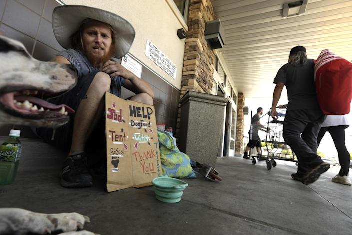 Anthony Wainscott, 33, and his dog, Roscoe, sit in 107-degree heat in Palmdale on Sunday.