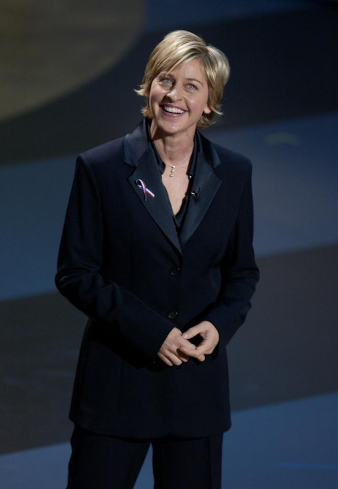 """Ellen Degeneres hosted the 53rd Primetime Emmy Awards in 2001.  The show was originally scheduled just days after the September 11th terrorist attacks but was pushed to November 4, 2001.  Ellen stared down the near impossible challenge of delivering comedy in the midst of tragedy.  But her performance was pitch-perfect, paying respect to those who lost their lives while giving audiences a much needed opportunity to laugh.  Her most memorable line of the evening summed up Hollywood's and, indeed, the country's undefeated, can-do spirit: """"They can't take away our creativity, our striving for excellence, our joy. Only network executives can do that.""""  She earned numerous standing ovations for her performance and went on to host a total of four Emmy Awards.  Above all, she reassured audiences that America would continue to create, to grow, and to laugh.(M. Caulfield/Getty Images)"""