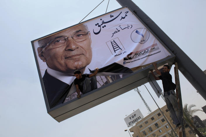 "Two laborers install an election poster for Egyptian presidential runoff candidate, Ahmed Shafiq, on the side of a highway in Cairo, Egypt, Monday, June 11, 2012. Shafiq faces the Muslim Brotherhood's candidate, Mohamed Morsi, in the June 16-17 runoff that could mean the difference between a secular state or one in which a hidden Islamist agenda slowly takes root. Arabic reads ""Ahmed Shafiq, President for Egypt."" (AP Photo/Nasser Nasser)"