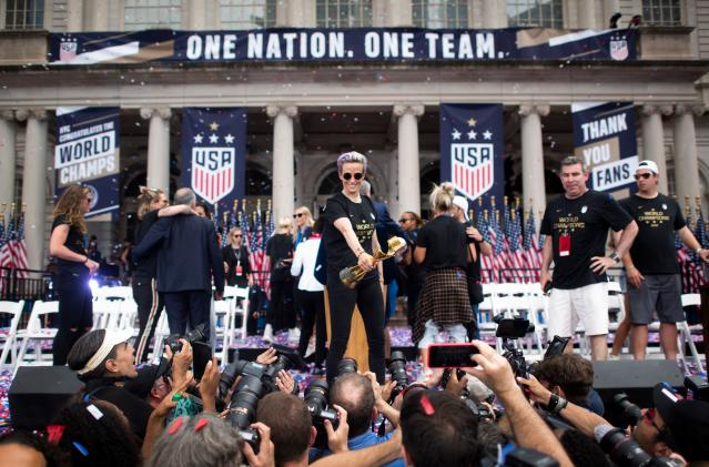 """USA women's soccer player Megan Rapinoe holds the trophy in front of the City Hall after a ticker tape parade for the women's World Cup champions on July 10, 2019 in New York. - Amid chants of """"equal pay,"""" """"USA"""" and streams of confetti, the World Cup-winning US women's soccer team was feted by tens of thousands of adoring fans with a ticker-tape parade in New York on Wednesday. (Photo by Johannes Eisele/AFP/Getty Images)"""