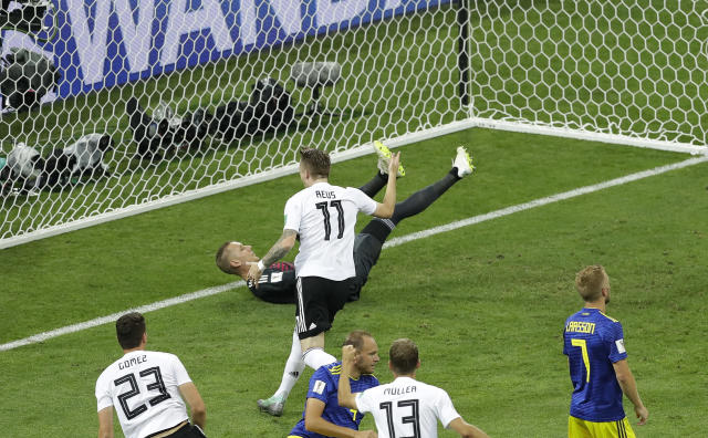 Germany's Marco Reus, middle, celebrates after scoring against Sweden goalkeeper Robin Olsen his side's first goal during the group F match between Germany and Sweden at the 2018 soccer World Cup in the Fisht Stadium in Sochi, Russia, Saturday, June 23, 2018. (AP Photo/Sergei Grits)