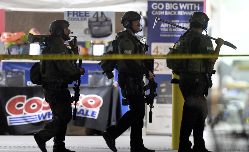 FILE - This June 14, 2019 file photo shows heavily armed police officers leaving the Corona, Calif., Costco store following a fatal shooting inside. A grand jury has declined to bring charges against an off-duty Los Angeles police officer who fatally shot Kenneth French during an altercation in the store. Riverside County District Attorney Mike Hestrin announced the grand jury's decision Wednesday, Sept. 25, 2019. (Will Lester/Inland Valley Daily Bulletin/SCNG via AP, File)