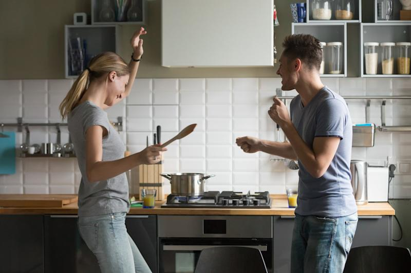 young man and woman smiling and dancing in kitchen