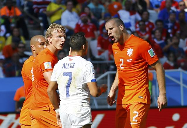 Chile's Alexis Sanchez (C) argues with Dirk Kuyt and Ron Vlaar (R) of the Netherlands during their 2014 World Cup Group B soccer match at the Corinthians arena in Sao Paulo June 23, 2014. REUTERS/Ivan Alvarado (BRAZIL - Tags: SOCCER SPORT WORLD CUP)