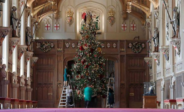 PHOTO: Staff adjust decorations on a Christmas tree in St George's Hall at Windsor castle during a media preview in Windsor, England, Nov. 29, 2019. (Alastair Grant/AP)