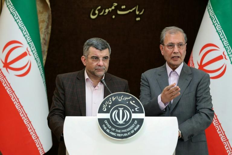 Iran's deputy health minister (L), who has tested positive for the novel coronavirus, coughed and wiped sweat from his brow during a press conference in Tehran on Monday with government spokesman Ali Rabiei