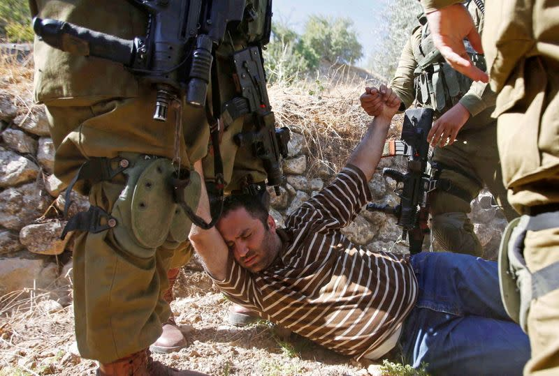 FILE PHOTO:Palestinian activist Issa Amro is detained by Israeli forces in the West Bank city of Hebron