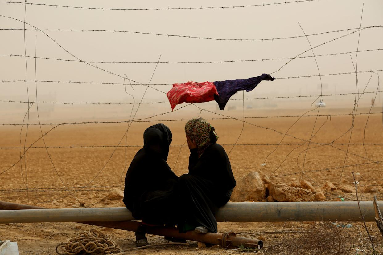 Syrian women sit next to the fence during a sandstorm at a temporary refugee camp in the village of Ain Issa, housing people who fled Islamic State group's Syrian stronghold Raqa, some 50 kilometers (30 miles) north of the group's de facto capital on November 10, 2016.