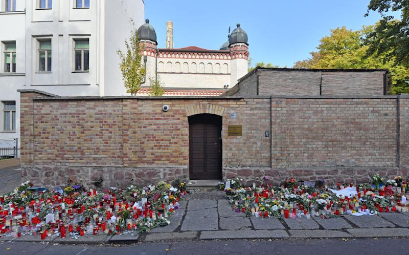 Flowers and candles are placed next to the door of the Halle synagogue, days after a right-wing extremist attack on the congregation. (Photo: Hendrik Schmidt/dpa-Zentralbild/dpa / picture alliance via Getty Images)