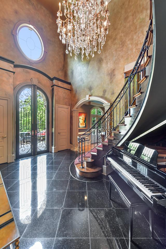 The entryway of the nearly 7,000-square-foot home opens into a sweeping staircase. (Photo credit: Josh Vick, HomeTour America)