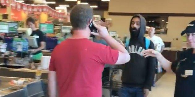 The man in the red, left, was warned by police after allegedly pushing and verbally accosting another shopper at Sobeys in London, Ont. on Wednesday.