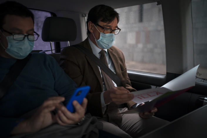 Catalan Socialist Party (PSC) candidate in the upcoming Catalan elections Salvador Illa, reads notes as he travels in a van ahead of a meeting in Barcelona, Spain, Monday, Feb. 8, 2021. A former health minister of Spain hopes to become a quiet political disruptor in the country's Catalonia region when voters go to the polls next weekend. (AP Photo/Emilio Morenatti)