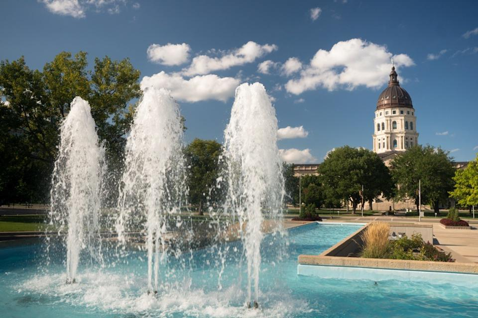 Soft clouds and blue skies appear over fountains and the capitol of Topeka, Kansas USA