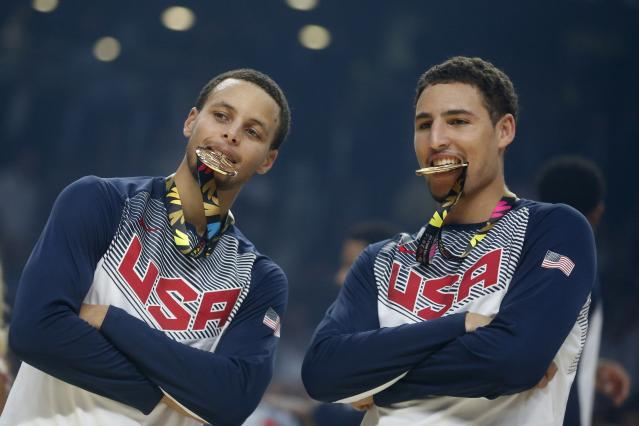 U.S. players Stephen Curry (L) and Klay Thompson bite their gold medals after winning their Basketball World Cup final game against Serbia in Madrid September 14, 2014. REUTERS/Juan Medina (SPAIN - Tags: SPORT BASKETBALL TPX IMAGES OF THE DAY)
