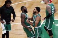Boston Celtics' Jayson Tatum (0) celebrates with Jaylen Brown (7) after making the go-ahead basket with less than a second on the clock during the second half of an NBA basketball game against the Milwaukee Bucks, Wednesday, Dec. 23, 2020, in Boston. (AP Photo/Michael Dwyer)
