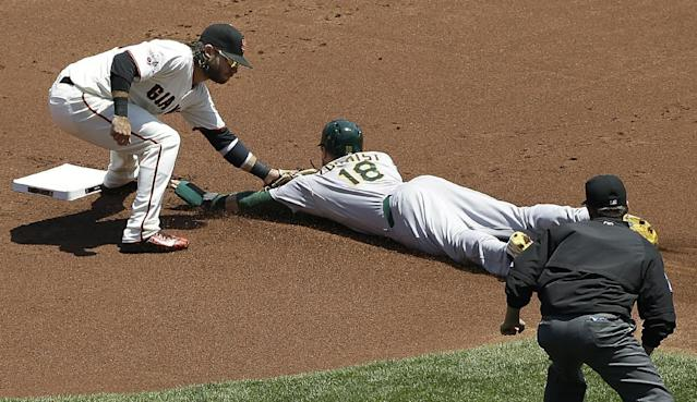 San Francisco Giants shortstop Brandon Crawford, left, tags out Oakland Athletics' Ben Zobrist (18) who was trying to steal second base during the first inning of a baseball game in San Francisco, Sunday, July 26, 2015. (AP Photo/Jeff Chiu)