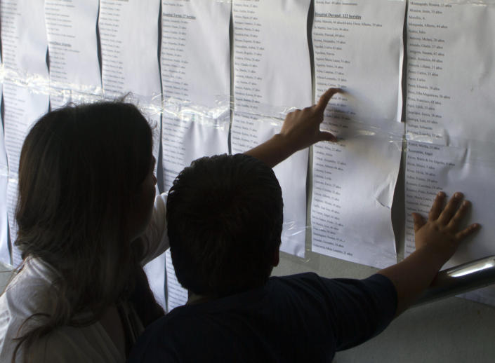 People look at lists of names informing what hospital injured commuters were sent to, posted outside the train station in Buenos Aires, Argentina, Thursday Feb. 23, 2012. Wednesday's commuter train crash killed dozens and sent hundreds to emergency rooms. A federal judge was leading an investigation into what caused the rush-hour commuter train to slam into a barrier at the end of the track at a downtown station, crumpling cars around hundreds of riders. (AP Photo/Eduardo Di Baia)