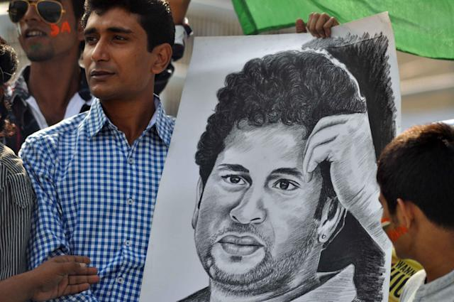 A Sachin fan holds his poster during the 1st day of the 1st test match between India and West Indies at Eden Gardens, Kolkata on Nov. 6, 2013. (Photo: IANS)