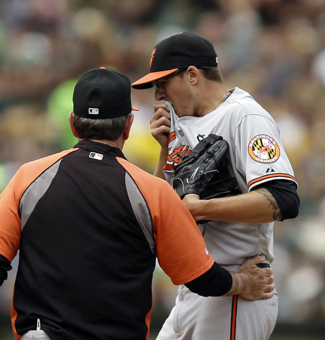 Baltimore Orioles' Kevin Gausman, right, wipes his face as he is visited by pitching coach Dave Wallace in the fourth inning of a baseball game against the Oakland Athletics Sunday, July 20, 2014, in Oakland, Calif. (AP Photo/Ben Margot)