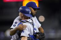 Los Angeles Dodgers relief pitcher Kenley Jansen, rear, hugs catcher Will Smith after the team's 3-0 win in a baseball game against the Arizona Diamondbacks on Friday, June 18, 2021, in Phoenix. (AP Photo/Ross D. Franklin)