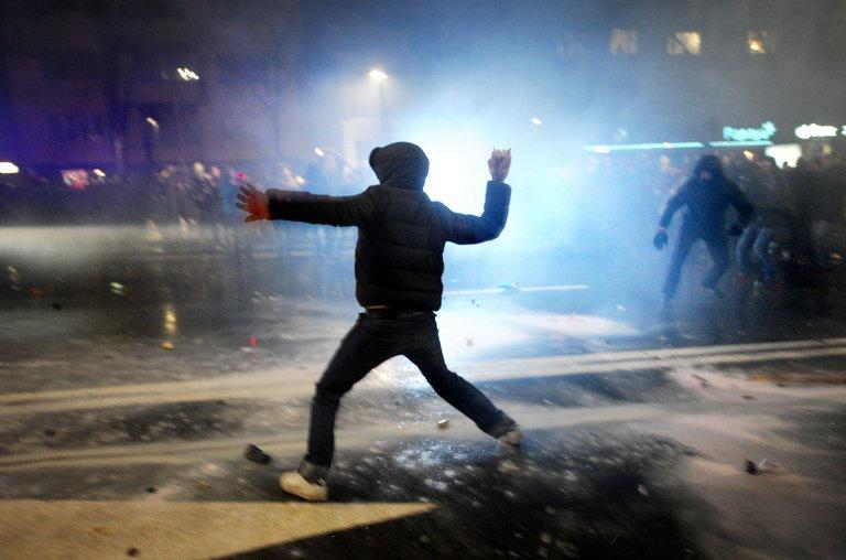A demonstrator throws a rock to riot police during clashes in downtown Sofia on February 19, 2013