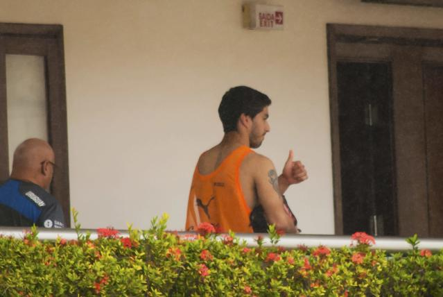 Uruguay's Luis Suarez gives a thumbs-up from a balcony of the team's hotel in Natal, June 26, 2014. Suarez was hit with the biggest ban imposed at a World Cup on Thursday as FIFA threw the book at one of soccer's most talented but controversial players for biting an opponent during the 2014 World Cup match against Italy. REUTERS/Leo Carioca (BRAZIL - Tags: SPORT SOCCER WORLD CUP)