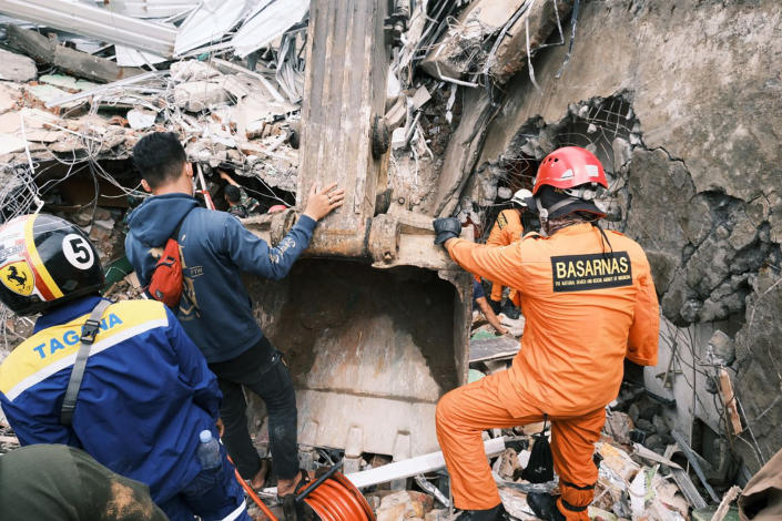 Rescuers search for victims at the ruin of a building damaged by an earthquake in Mamuju, West Sulawesi, Indonesia, Saturday, Jan. 16, 2021. Damaged roads and bridges, power blackouts and lack of heavy equipment on Saturday hampered Indonesia's rescuers after a strong and shallow earthquake left a number of people dead and injured on Sulawesi island. (AP Photo/Sadly Ashari Said)