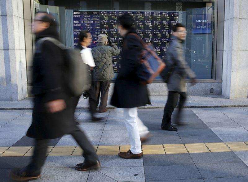 Man looks at an electronic stock quotation board as passers-by walk past, outside a brokerage in Tokyo