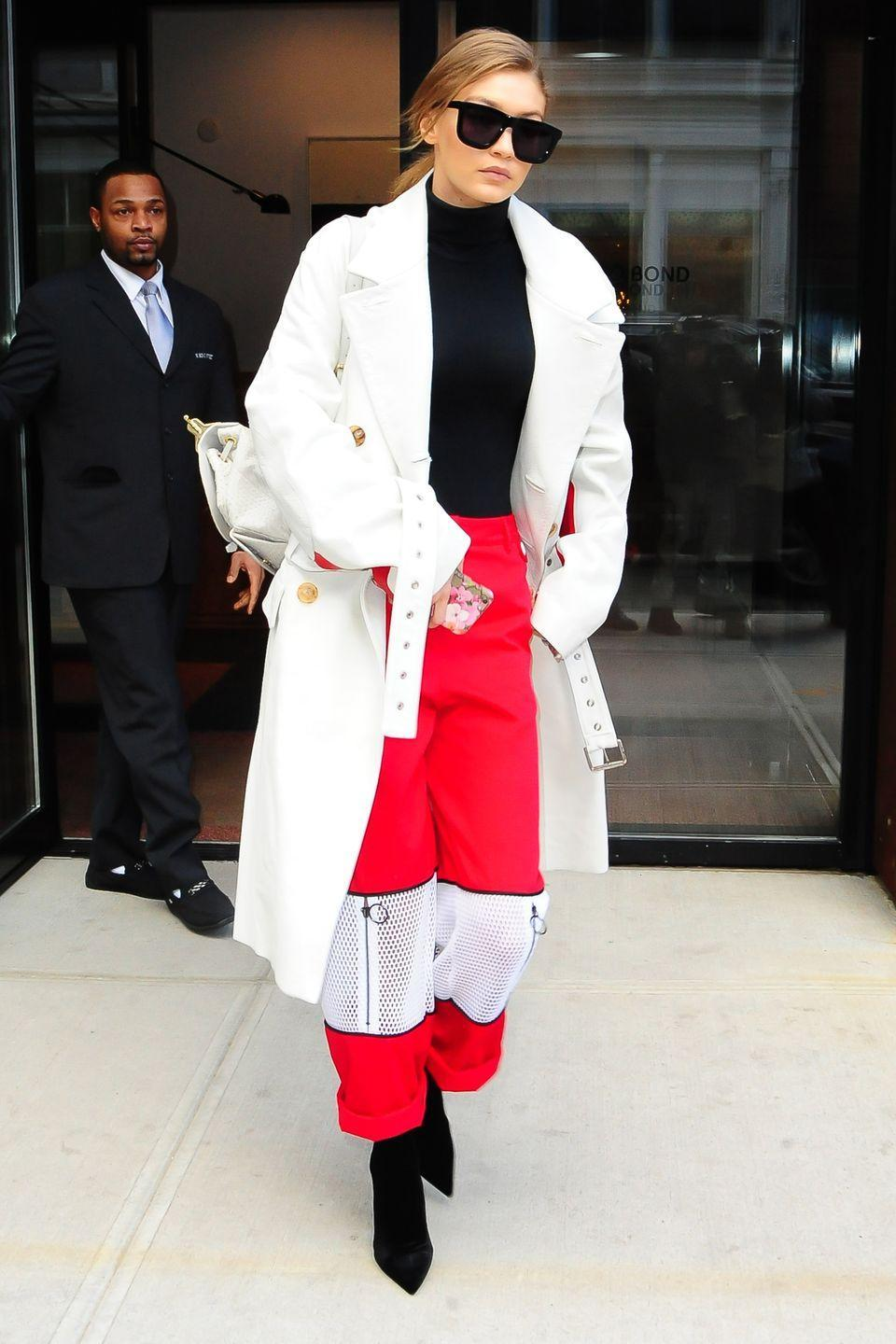 <p>In red pants with white zip-up mesh panels, a white coat, black turtleneck, black ankle boots and Karen Walker sunglasses while out in New York. </p>