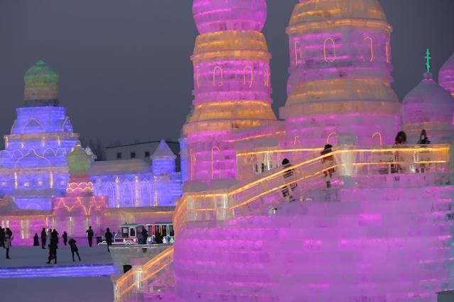 <p>People visit the ice sculptures illuminated by colored lights for the 34th Harbin International Ice and Snow Sculpture Festival on Jan. 4. (Photo: Wu Hong/EPA-EFE/REX/Shutterstock) </p>