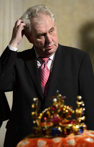 FILE-In this May 9, 2013 file photo, Czech President Milos Zeman scratches his head during a ceremonial movement of the Czech Crown Jewels for a rare showing to the public from the Crown Jewels chamber in the St. Vitus Cathedral to the Vladislav Hall at the Prague Castle. The Crown of Saint Wenceslas is seen in front. Was he or wasn't he? The video footage shows the new Czech president clearly worse for wear, propping himself up against a wall at a public event, struggling to negotiate a step and being aided by a cardinal. Milos Zeman makes no secret of his drinking. But on this occasion _ a rare and highly-ceremonial public display of the Czech crown jewels last week _ his office insisted he simply had a virus and subsequently needed a day or two of rest. (AP Photo/CTK, Michal Kamaryt) SLOVAKIA OUT