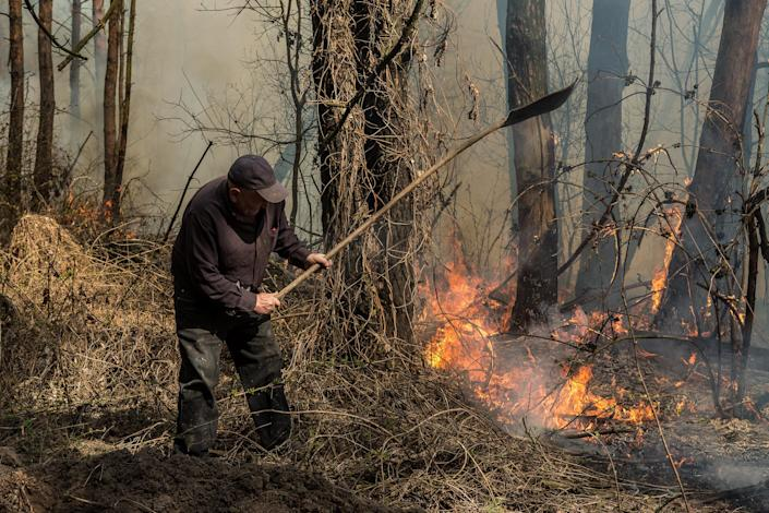 Image: A forest ranger with the Poliskyi Distrcit State Forestry Agency prevents the spread of a fire near Krasiatychi, Kyiv region (Oksana Parafeniuk / for NBC News)