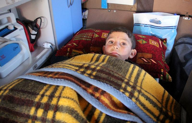 Nine-year-old Syrian Abdel Basset Al-Satuf (C) is seen inside an ambulance in the town of Al-Hbeit on February 17, 2017, ahead of being transferred to Turkey for medical treatment after being caught in a barrel bomb attack by regime forces