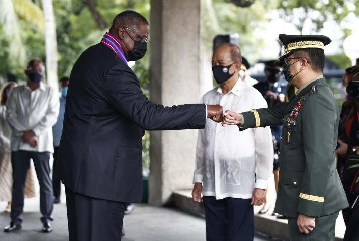United States Defense Secretary Lloyd Austin, left, greets Armed Forces of the Philippines Chief of Staff General Cirilito Sobejana, right, as Philippines Defense Secretary Delfin Lorenzana (C) looks on at Camp Aguinaldo military camp in Quezon City, Metro Manila, Philippines Friday, July 30, 2021. Austin is visiting Manila to hold talks with Philippine officials to boost defense ties and possibly discuss the The Visiting Forces Agreement between the US and Philippines. (Rolex dela Pena/Pool Photo via AP)