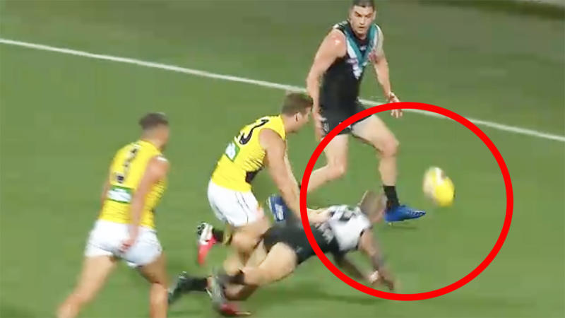 Port Adelaide's Hamish Hartlett is seen deliberately knocking the ball out of bounds against Richmond.