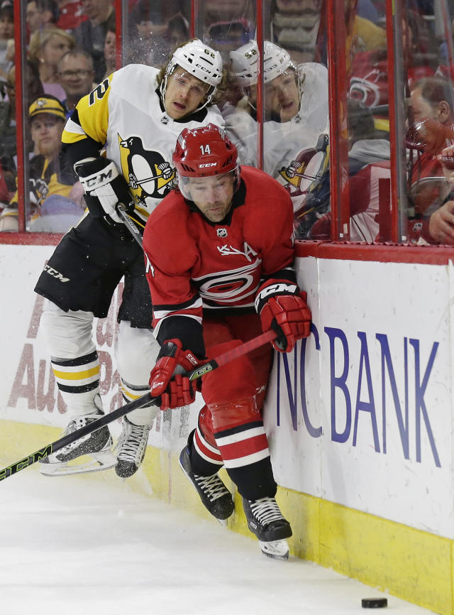 Carolina Hurricanes' Justin Williams (14) and Pittsburgh Penguins' Carl Hagelin (62), of Sweden, skate for the puck during the first period of an NHL hockey game in Raleigh, N.C., Friday, Feb. 23, 2018. (AP Photo/Gerry Broome)