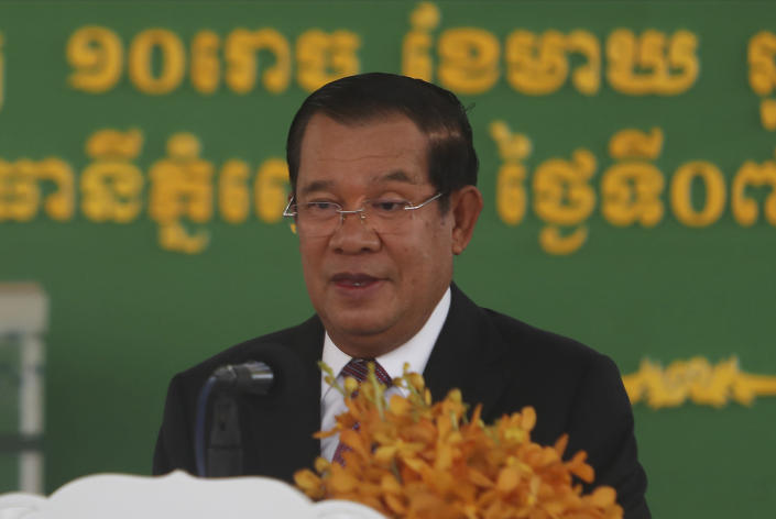 """Cambodian Prime Minister Hun Sen smiles as his delivers a speech during a handover ceremony at Phnom Penh International Airport, in Phnom Penh, Cambodia, Sunday, Feb. 7, 2021. Cambodia on Sunday received its first shipment of COVID-19 vaccine, a donation of 600,000 doses from China, the country's biggest ally. Beijing has been making such donations to several Southeast Asian and African nations in what has been dubbed """"vaccine diplomacy,"""" aimed especially at poorer countries like Cambodia. (AP Photo/Heng Sinith)"""