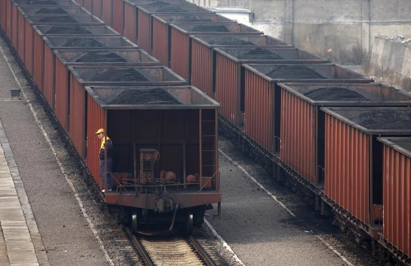 FILE PHOTO: A worker stands on a wagon of a coal train as it tranfers coal to a power plant in Huaibei