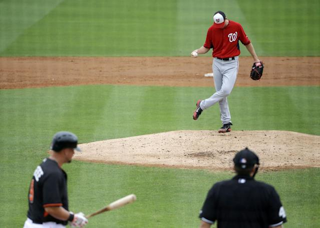 Washington Nationals starting pitcher Taylor Jordan, right, kicks the dirt on the mound before throwing to Miami Marlins' Casey McGehee, left, in the second inning of an exhibition spring training baseball game, Monday, March 24, 2014, in Jupiter, Fla. (AP Photo/David Goldman)