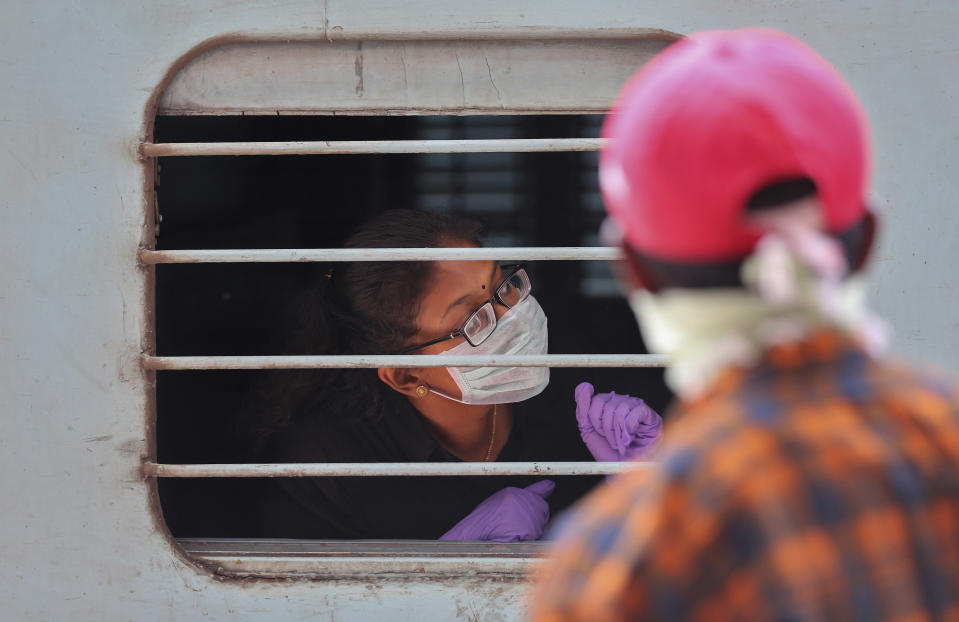 An Indian passenger wearing face mask and gloves as a precaution against COVID-19 peeps out of a train window at Secunderabad Railway Station in Hyderabad, India, Saturday, March 21, 2020. For most people, the new coronavirus causes only mild or moderate symptoms. For some it can cause more severe illness. (AP Photo/Mahesh Kumar A.)