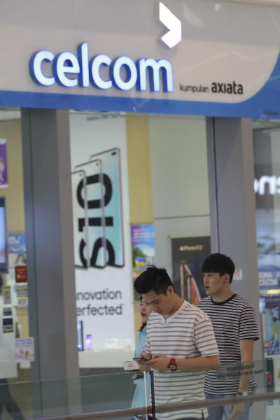 Customers walk past a Celcom mobile telecom outlet on Monday, May 6, 2019, in Putrajaya, Malaysia. Malaysia's Axiata Group Berhad says it is in talks with Norway's Telenor ASA to merge their Asian operations to create one of the world's top telecommunications giants with some 300 million customers in nine countries.(AP Photo/Vincent Thian)