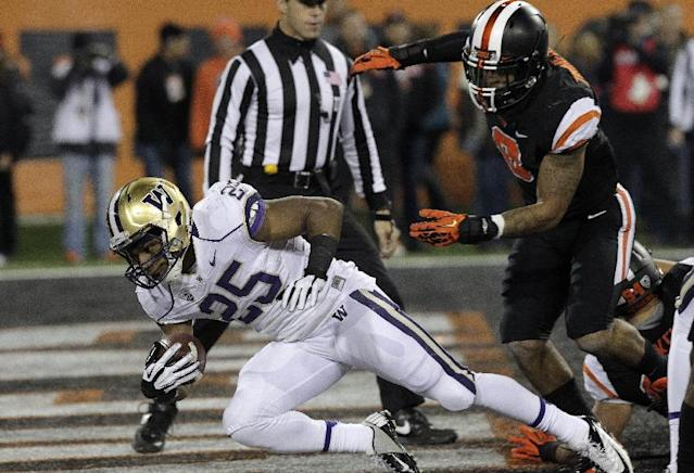 Washington running back Bishop Sankey, left, dives in for a touchdown past Oregon State defender Tyrequek Zimmerman during the first half of an NCAA college football game in Corvallis, Ore., Saturday, Nov. 23, 2013. (AP Photo/Don Ryan)