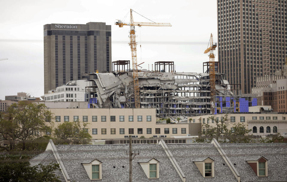 Debris hangs on the side of the building after a large portion of a hotel under construction suddenly collapsed in New Orleans on Saturday, Oct. 12, 2019. Several construction workers had to run to safety as the Hard Rock Hotel, which has been under construction for the last several months, came crashing down. It was not immediately clear what caused the collapse or if anyone was injured. (David Grunfeld/The Advocate via AP)