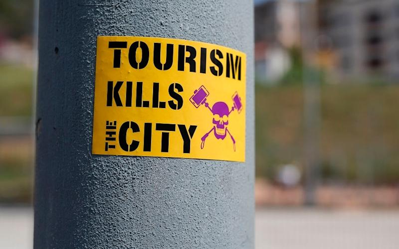 An anti-tourism sticker adorns a lamp-post in Barcelona - This content is subject to copyright.