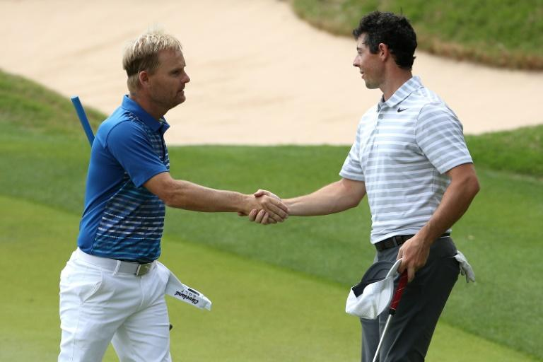 Soren Kjeldsen (L) of Denmark shakes hands with Rory McIlroy of Northern Ireland after round one of the World Golf Championships Match Play, at the Austin Country Club in Texas, on March 22, 2017