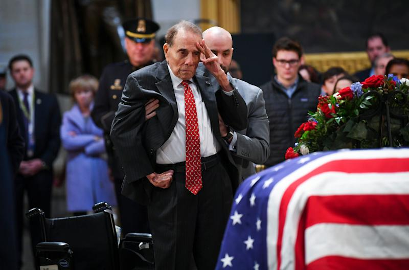 Former Sen. Bob Dole stands and salutes the casket of President George H.W. Bush who lies in state at the U.S. Capitol Rotunda.